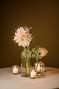 Vintage clear glass bud vases with blush dahlias, roses, and greenery