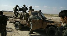 Armed men in uniforms identified by Syrian Democratic forces as US special operations forces stand in the back of a pickup truck in the village of Fatisah in the northern Syrian province of Raqa on May 25, 2016