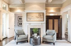 "The living room is welcoming with custom club chairs, a resin drum table from Oly and limestone fireplace. A TV provides entertainment options for the room but is hidden away within an armoire from Robert Lighton when not in use. Above the mantel hangs ""Deer in a Gentle Landscape""; a favorite from the client's collection of Asian screens. Completing the design are a grasscloth wallcovering from Philip Jeffries and a wool rug from Merida's John Mahoney collection."