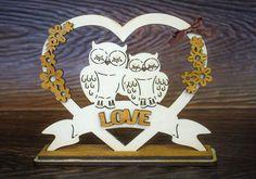 Сувенир «Совушки» в сердце сделан из березовой фанеры и окрашен морилкой, что позволяет сохранить дереву его натуральный вид. Сувенир имеет средние размеры 12 см в длину, 10 см в высоту и 3 см в ширину. За счет двойного дна композиция устойчиво стоит на ровных поверхностях.  Надпись «love», парочка влюбленных сов и огромное сердце, - вот основные элементы сувенирной композиции «Совушки». Этот сувенир хорошо разместится на столе или полке и будет напоминать о высоких чувствах и бесконечно…