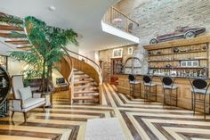 Dimensional geometric hardwood floors with curved staircase leading up to second floor with indoor overlook and balcony and light brick walls behind bar in living room
