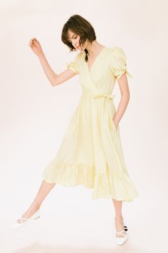 Lovely wrap dress with tie sleeve detail and side pockets. Fitted bodice with full skirt and ruffle hem. Adjustable tie waist for your perfect fit and comfort. Made in surplus lemon-coloured linen, saving the fabric from landfills.