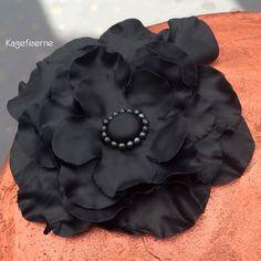 Black fondant flower on bronze-colored cake – Sort fondant blomst på bronzefarvet lagkage.
