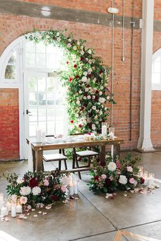 Flower installation wedding floral burgundy and cream white ground arrangements candles roses smilax greenery installation curved arched doorway at Brick Liberty Station Wedding Reception Table Decorations, Bridal Table, Wedding Table Settings, Wedding Ideas, Table Wedding, Farm Wedding, Wedding Couples, Garden Wedding, Floral Wedding