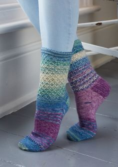 Socks are worked in the round from the top down. The cuff is folded in half to form the picot edge and sts from the cast-on edge are knitted with sts on next row to create a cuff hem. A slip stitch pattern is worked on the leg, and the foot is worked in stocking stitch. To avoid a sudden break in the colour variation pattern across the top of the foot when you work the heel, wind off about 40m of yarn before you start. Use this yarn to work the heel flaps and heel turns, then break off this…