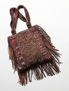 Say yes to wanderlust with this intricately embellished leather and cloth tote, featuring handmade tapestry accents, ornate leather embroidery, tonal hand-stitching, and cascading fringe trim. Hidden magnet closure. Interior lined; features pockets.