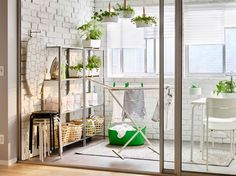 A balcony with shelving units in galvanized steel and a white drying rack with two fold-out wings.