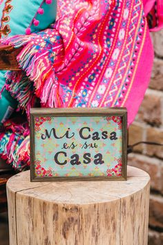 """Decorate your home with some Mexicali flair! The Mi Casa Mini Wall Sign is the perfect decorative accent for any room in your home or apartment. A wood border and colorful background add beautiful touches to this wall piece. Pair with our additional home & wall decor options to complete your look.<br /> <br /> - 7.5"""" x 9.5""""<br /> - Colorful floral background<br /> - Wooden border<br /> - Black font<br /> - Imported<br />"""