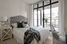 Chic city bedroom design with gray tufted headboard, ivory mirrored nightstands, mercury glass lamps, black & gray throw and white curtains window panels.