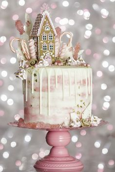 Pink Gingerbread Dream House Drip Cake by Veronica Arthur. Gingerbread cake, whipped white chocolate ganache filling, water color buttercream and white chocolate ganache drip. Handmade toppers: Gingerbread house, gingerbread fondant rosettes, pink meringue kisses with gingerbread man sprinkles, white chocolate chards with crushed candies. Join my Gingerbread Dreams Facebook group for my secret fondant and gingerbread recipes. #Gingerbread #GingerbreadHouse #GingerbreadDripCake #DripCake