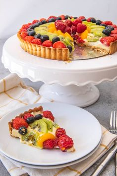 An image of a fresh fruit tart on a white cake stand, with one slice cut and served on a white plate. An image of a fresh fruit tart on a white cake stand, with one slice cut and served on a white plate. French Fruit Tart Recipe, Fruit Tart Glaze, Fresh Fruit Tart, Fruit Flan Recipe, Mini Fruit Tarts, Easy Fruit Tart Recipe, Fruit Custard Tart, Juicy Fruit, Fruit Tartlets