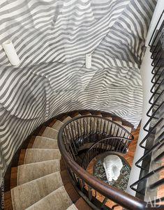 Ограждение лестницы сделано из бронзы иореха. Обои напечатаны вручную вкомпании Janet Yonaty иимитируют ниспадающую складками ткань. Шелковый ковер, Lindstrom Rugs.