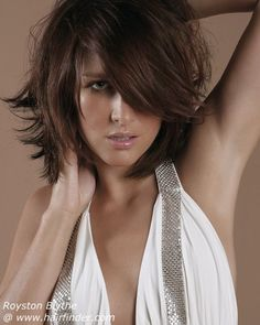shoulder-length bob with box layering in lower third of hair & long, textured fringe   (use a flat brush when blowing out to keep the curl to a minimum)