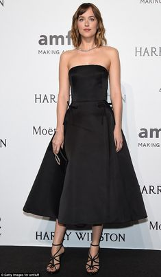 Classic glamour: Dakota Johnson wowed in a black strapless gown as she kept up with the fash-pack at the amfAR gala during Milan Fashion Week on Saturday night
