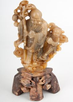 Description An elaborate Chinese soapstone carving of Shou Lao & an attendant Carrying a peach & a large gnarled staff, on a base of a different hue  Date 20th century  www.collectorstrade.de