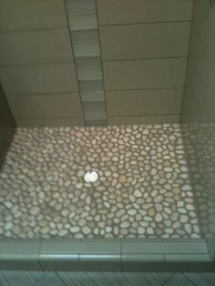 stone shower floor..looks pretty but i wonder if it would be harsh on the feet. .