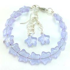 Komplet biżuterii wykonany ręcznie. Bransoletka z kolczykamiw kolorzeliliowym(bardziej nasyconym) ze szklanymi koralikami i elementami ozdobnymi.