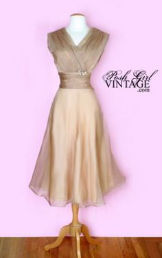 1950's Light Beige Organza Tea Length Dress This stunning early 50's vintage dress would make the perfect vintage wedding dress! The sheer organza is beautiful in a light beige color with a crystal rhinestone broach. Fully lined in rayon of the same color. Metal zipper on one side, surplus neckline... A classic!