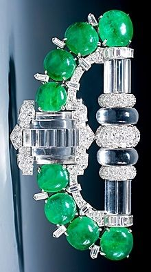 A magnificent Art Deco rock crystal, emerald and diamond clip brooch, set with 8 cabochon emeralds, carved rock crystal and baguette cut, old European cut and single cut diamonds, mounted in platinum and 18 karat gold. Circa 1937-38, unsigned, accompanied by the Mauboussin certificate of authenticity, stating that this brooch was made by Trabert & Hoeffer - Mauboussin between 1937 and 1938.