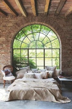 Exposed brick, arch window with small panes, intricately detailed fabric, garden view