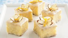 Bite-sized citrus cakes are drizzled with a sweet apricot icing then topped with sliced almonds and orange peel.