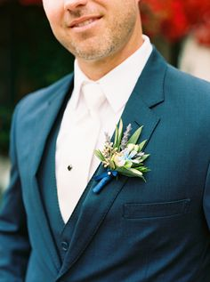 Chic boutonniere with lavender, olive leaves, tweedia, and eucalyptus. Fleurish Floral Designs