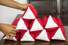 How to make (sew) Thai triangle cushions (pillows composed of a stacked, sewn-together series of ten separate triangle cushions). Traditionally, Thai triangles are filled with straw to create a firm pillow to rest against, but today they are usually filled with tightly packed batting for firmness. The cushions come in a variety of colors and are used for comfort...