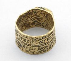 Love-ring; gold; engraved; broad flat hoop divided horizontally by milled band, inscription on exterior, inscribed interior depicts woman and squirrel among flowers and foliage; circular bezel containing sapphire bead.