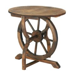 "Wagon Wheel Table - Rustic chic is in, and this wagon wheel table is the perfect example of how that rustic charm complements your decor. Made from fir wood and iron, this cool accent table features a round top that sits over an old-fashion wagon wheel base. Made from fir wood and iron. Some assembly required.  Dimensions: 20"" tall x 22"" diameter"