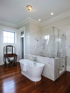 The freestanding soaker tub is the focal point of this bathroom with a frameless shower, glass enclosure to allow for a perfect view of the tub upon entry. The amount of grey and marble detail creates interest and adds to the serenity. Cherry wood floors and antique make-up table add warmth to this contemporary space.