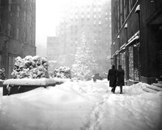 Glistening in the snow, the landmark Christmas tree at New York's Rockefeller Plaza stands out in the distance as pedestrians make their way through the snow drifts of one of the heaviest winter storms in years on Dec. 26, 1947.