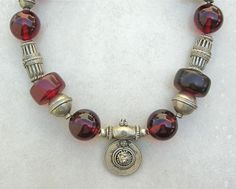 Necklace made from using pieces out of an antique Yemeni necklace, four cylinder shaped cherry coloured African amber beads (early to mid 1900s) and six new reconstituted cherry amber beads by Sandra Destash.