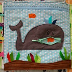 cute page from a cloth quiet book showing a whale's open mouth made with a zipper & a little fishy inside, from the jennie's threads blog