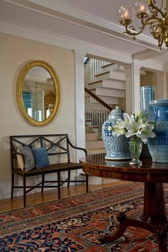This traditional entryway features a golf-leaf mirror, antique chandelier and an oriental rug to complete a classic look. Flowers and dark wood finishes give the space a more warm and inviting feel. Decor, Round Rug Living Room, Interior, Southern Decor, Home, Beautiful Interiors, Entryway Decor, House Interior, Blue White Decor