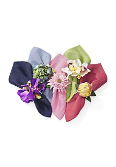 No need for a centerpiece at your next dinner party. These handmade napkin rings featuring silky orchids, zinnias, peonies and hydrangeas are even more luxurious wrapped around line napkins in a bouquet of shades.