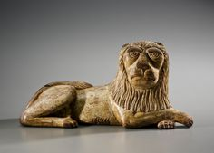 """Carved and painted figure of a recumbent lion Bucks County, Pennsylvania, circa 1830 Poplar, original ivory paint, 6 ½ x 12 x 4 ½ inches. This lion is one of a pair, the mate illustrated in Frances McQueeney-Jones Mascolo, """"Eagles & Tulips, Snakes & Weathervanes, A Pennsylvania Folk Art Collection,"""" Antiques & Fine Art, Spring 2009, page 123. The pose and characterization displayed in this pair of lions is similar to the ones depicted in Peaceable Kingdoms painted by Edward Hicks (1780-1839)"""
