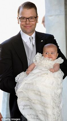 Crown Princess Victoria, who married her former gym trainer Daniel in a ceremony in 2010, hold Princess Estelle, wearing a gown that has been used for Swedish royal christenings since 1907