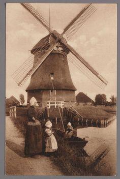 De watermolen in de Volendammer polder. Moeder en kind in dracht links op het pad. In de vlet een breiend meisje. 1905-1920 #NoordHolland #Volendam