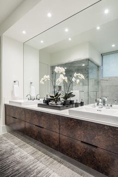 Rich burl floating vanity contrasts against cararra marble flooring and wall tile. Accents of gray and black mix perfectly with the chrome plumbing fixtures. Stephen Allen Photography