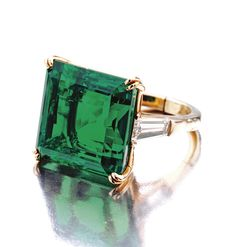 SUPERB EMERALD AND DIAMOND RING, VAN CLEEF & ARPELS, NEW YORK, 1968. The emerald-cut emerald weighing 18.54 carats, flanked by 2 tapered baguette diamonds weighing 1.23 carats, mounted in 18 karat gold, size 5½, signed VCA, numbered NY 4144 SO. With signed box.