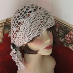 Image from https://static2.artfire.com/uploads/product/6/806/76806/5876806/5876806/large/womens_crochet_hat_pattern_open_mesh_wrap_with_button_trim_pdf_a68511ae.jpg.
