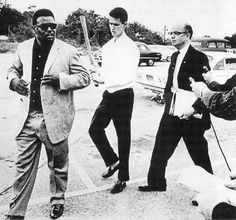 """1964: Lester Maddox with a gun (right) and his son wielding an ax handle (center), ""escorting"" a Black man trying to eat at his whites-only chicken restaurant Pickrick Cafe, in Georgia. Maddox said that he would close his restaurant rather than serve African Americans. Maddox went on to become the governor of Georgia in 1967."""