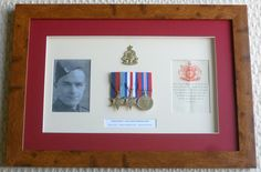 WW2 memorabilia picture frame containing containing 39/45 Star Medal,   France & Germany Star Medal and the 39/45 War Medal. Also a photo, certificate of issue for the medals and a cap badge.