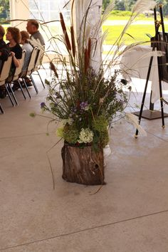 Rustic floral arrangement in a hollow tree stump at my daughters wedding.
