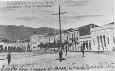 """Ενα από τα πολλά ονόματα που είχε κατά καιρούς η κεντρική πλατεία της Καλαμάτας ήταν και """"Λαϊκής Σχολής"""".  Από το κτήριο που στέγαζε την ομώνυμη σχολή και σήμερα αποτελεί αρχιτεκτονικό στοιχείο του Πνευματικού Κέντρου.      [Φωτογραφία της δεκαετίας του 1920 από καρτ ποστάλ]."""