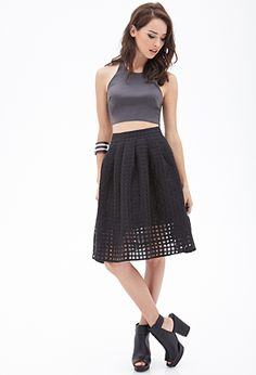We love the thrill of frills, but sometimes we want the feeling without the frilliness. Enter this gorgeous pleated windowpane skirt. Its girlish silhouette is balanced by the graphic quality of the sheer overlay. Team this knee-length piece with a moto jacket for a femme mix of hard and soft.