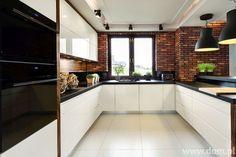 Nowoczesna kuchnia z naturalną cegłą w tle.