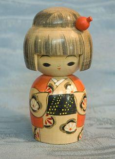 Vintage Kokeshi doll with orange and black kimono.