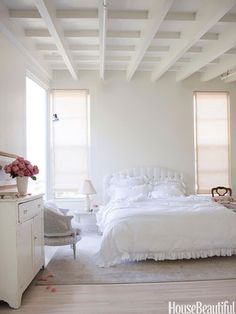 Photographer Amy Neunsinger transformed her Los Angeles home into a simple yet modern home. In the master bedroom, the pickled white wood floors combined with white walls create an ethereal feeling. The headboard and bedding are from Shabby Chic.   - Veranda.com