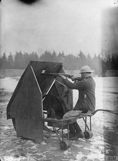 A French soldier behind a mobile gun shield on the Aisne front, February 10, 1916.
